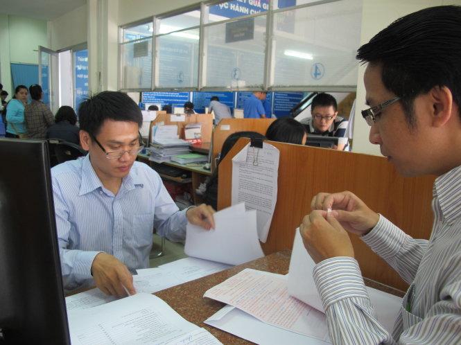 Cán bộ thuế hướng dẫn người dân làm thủ tục quyết toán thuế thu nhập cá nhân tại Cục Thuế TP.HCM - Ảnh: ÁNH HỒNG